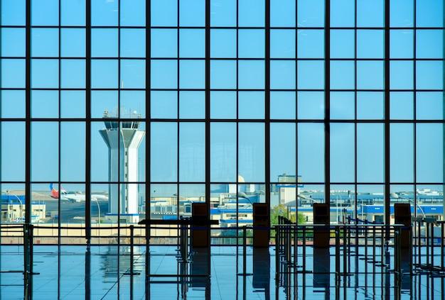 활주로를 볼 수있는 유리 쇼케이스 공항 건물.