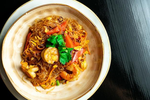 ガラスのエビと暗い背景に黄色のボウルに野菜のシンガポール麺。