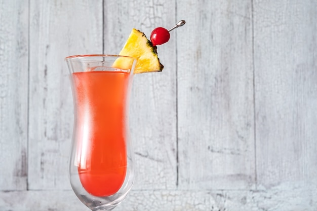 Glass of singapore sling on wooden background