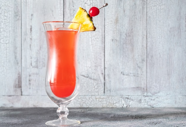 Glass of singapore sling on wooden table