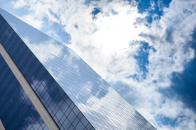 Glass skyscraper against cloudy blue sky, strongly reflective windows