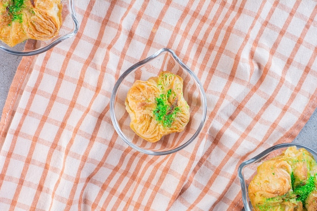 Glass small platters with three delicious baklawas on tablecloth