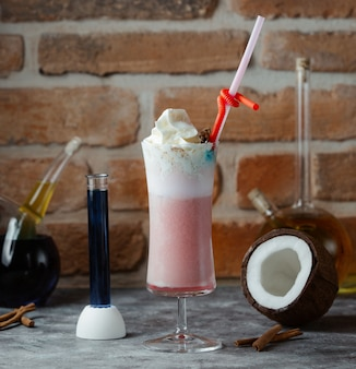 A glass of smoothy with whipping cream in the top and chopstick.