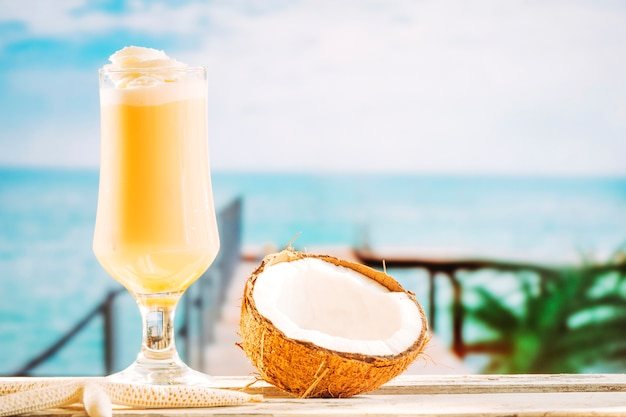 Glass of soft yellow drink starfish and cracked coconut