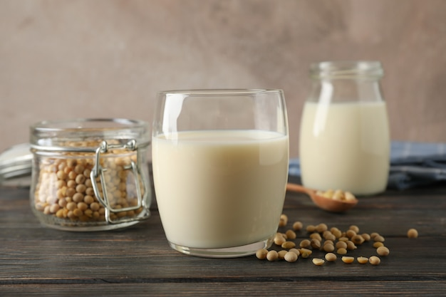 Glass of soy milk, soybeans seeds on spoon, napkin on wooden table