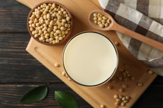 Glass of soy milk and soybeans seeds on wooden