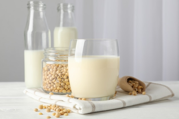 Glass of soy milk, soybeats seeds, bottle with milk on white, space for text