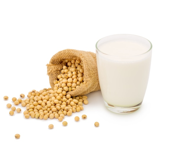 Glass of soy milk with soybeans in bag isolated on white space.
