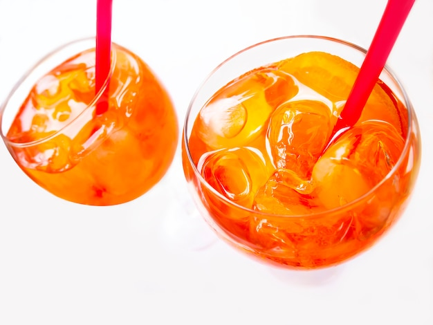 Glass of sparkling aperol spritz cocktails with straws isolated on white