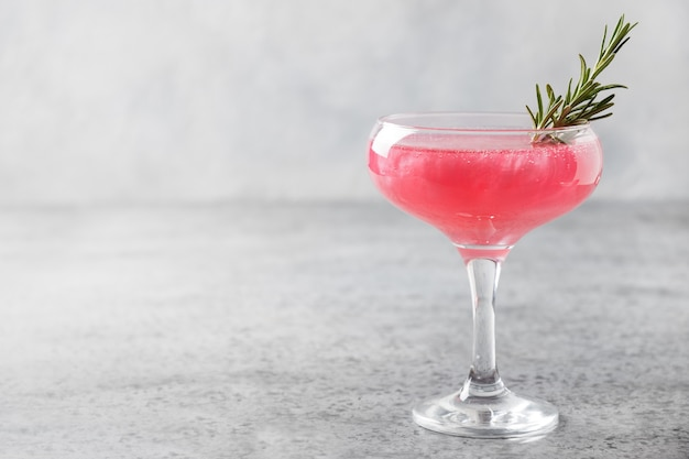 Glass of sparkling rose wine with shimmer edible glitter garnish rosemary on grey.