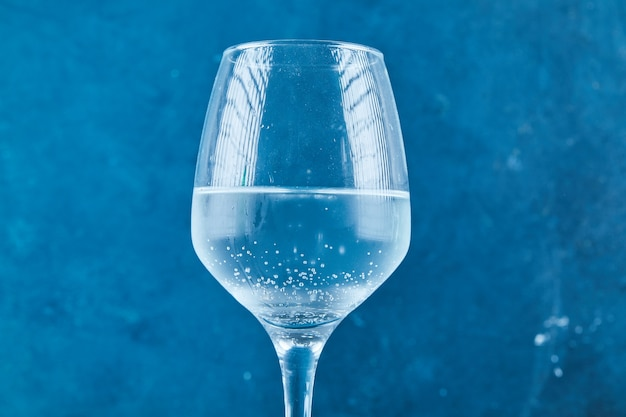 A glass of sparkling water on blue surface