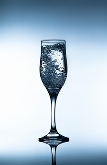 Glass of sparkling water on gradient