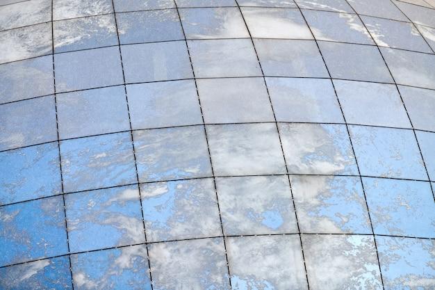 푸른 하늘과 구름의 반사와 유리 구형 현대 건물.