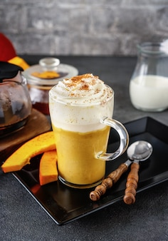 A glass of spicy pumpkin cappuccino on grey