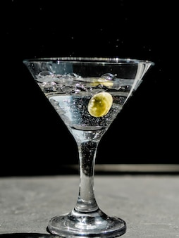Glass of splashing martini with olive