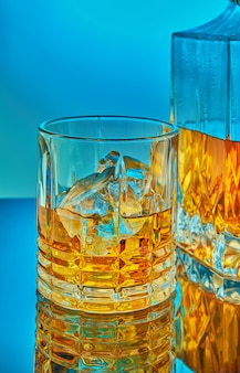 A glass and square crystal decanter with scotch whiskey or brandy in the background on a blue gradient background with reflection