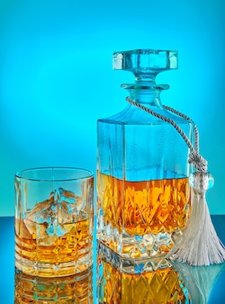 Glass and square crystal decanter with scotch whiskey or brandy on a blue gradient background with reflection