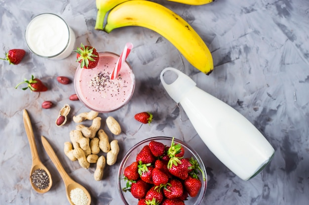 A glass of strawberry banana smoothie among the ingredients for its cooking