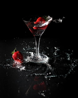 Glass of strawberry cocktail on a black
