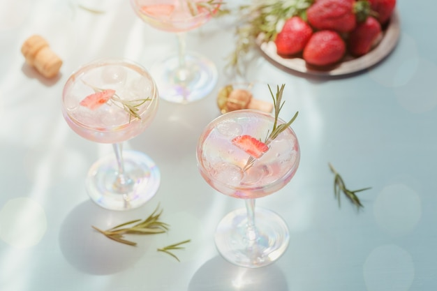 Glass of strawberry cocktail or mocktail, refreshing summer drink with crushed ice and sparkling water on light blue