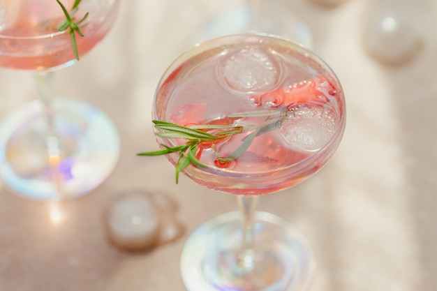 A glass of strawberry cocktail or mocktail, refreshing summer drink with crushed ice and sparkling water on light