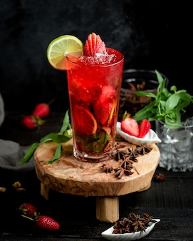 A glass of strawberry cocktail with strawberries and lime slices