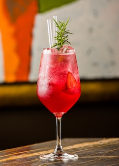 A glass of strawberry cold cocktail with fresh rosemary leaves and pipes