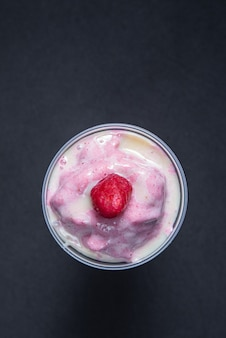 Glass of strawberry milk shake or cream on the black table