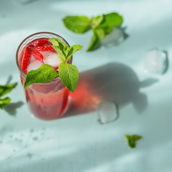 Glass of strawberry soda drink on light blue background