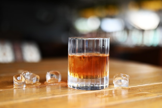 A glass of strong alcohol whiskey or rum on the table in a restaurant with ice