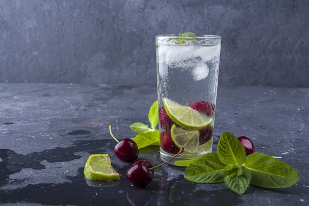 Glass of summer lemonade or ice tea. refreshing cool detox drink with cherry and mint on dark background.