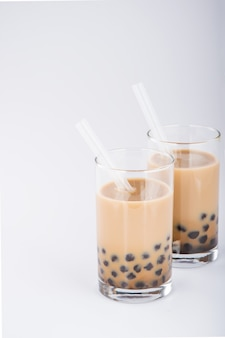 A glass of sweet milk bubble tea with tapioca pearls, and straw on white background. copy space