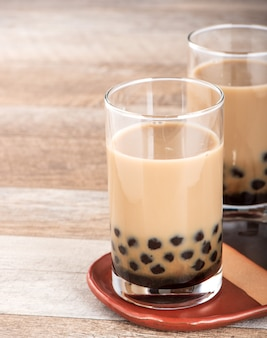 A glass of sweet milk bubble tea with tapioca pearls, and straw on wooden background. copy space