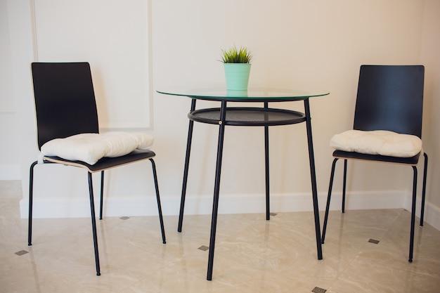 ガラステーブルとダイニングルームの白いモダンな椅子。