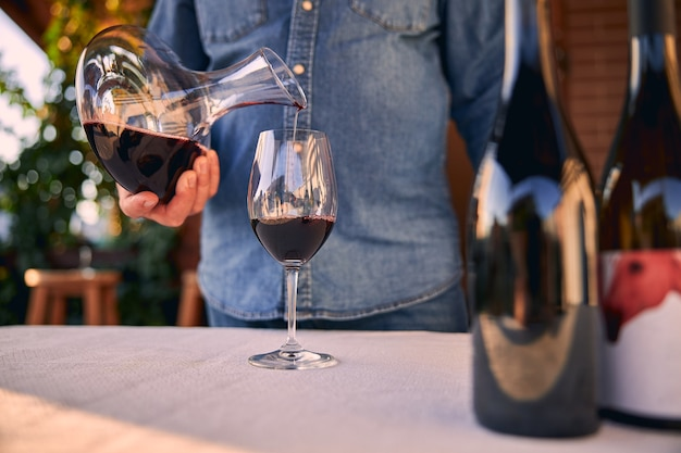Glass on the table and a man in denim shirt pouring red wine into it from the decanter