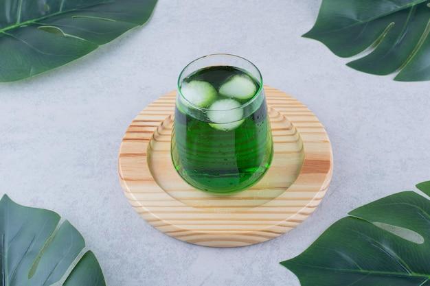 Bicchiere di succo di dragoncello con ghiaccio sul piatto di legno. foto di alta qualità