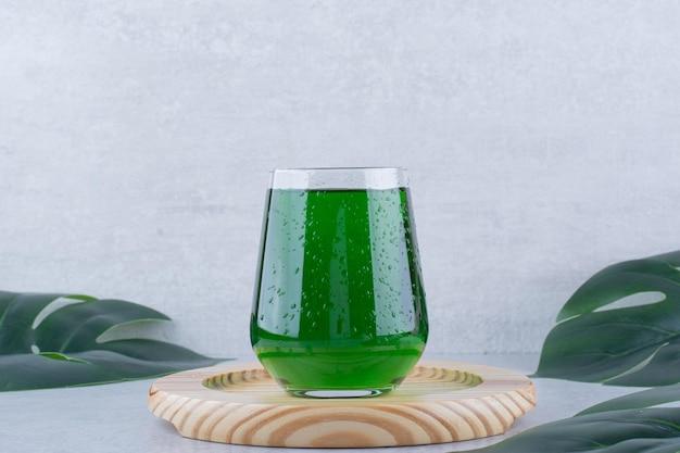 Bicchiere di succo di dragoncello sul piatto di legno. foto di alta qualità