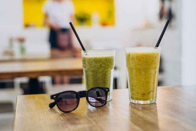 Glass of tasty healthy smoothie on table in summer cafe.