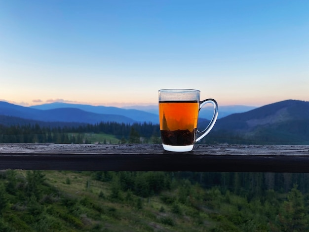 Glass of tea on carpathian mountains view on sunrise. ukraine, dragobrat