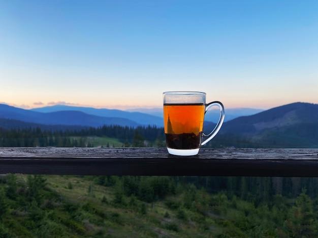 Glass of tea on carpathian mountains view on sunrise. ukraine, dragobrat