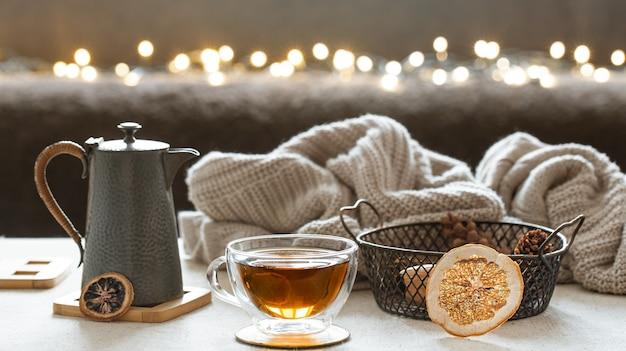 Стеклянная чашка чая и чайник с вязанным элементом на размытом фоне. понятие домашнего уюта и тепла.