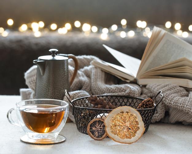ガラスのティーカップ、ティーポット、ニット要素の本。家の快適さと暖かさの概念。