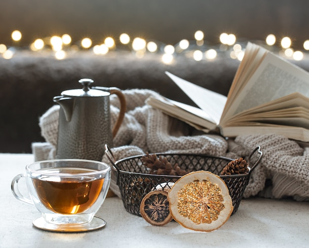 Glass tea cup, teapot and book with knitted element. the concept of home comfort and warmth.