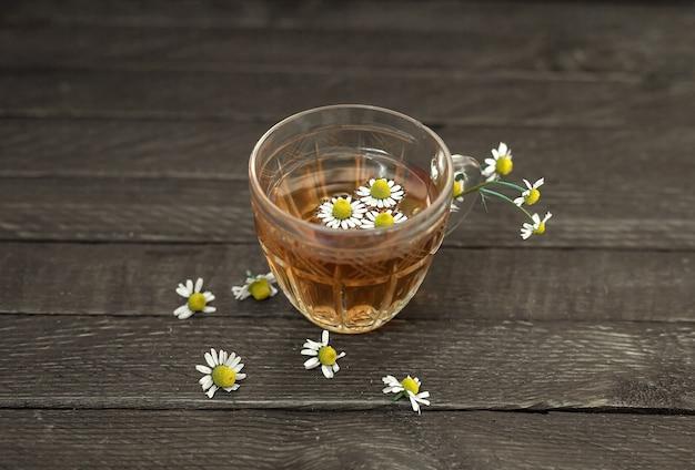 木製の背景にカモミールとガラスのティーカップ。カモミールの花が散らばっています。