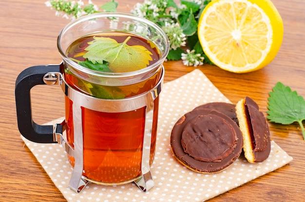 Glass of tea, fresh lemon balm and cookies on table.