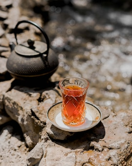 A glass of tea on the ground with black iron kettle.