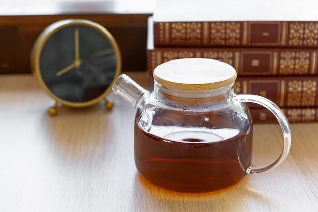 Glass tea pot with black tea on wooden table