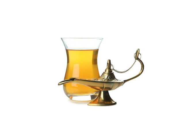 Glass of tea and ramadan lamp isolated on white