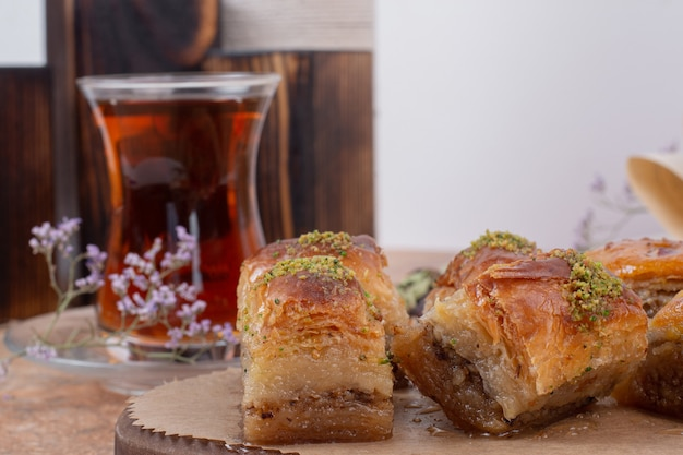 Glass of tea and traditional pistachio baklava on marble table.