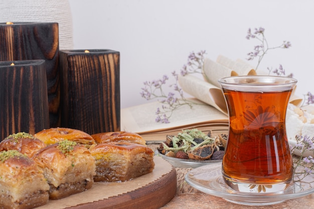 Glass of tea and traditional various baklavas on marble table.